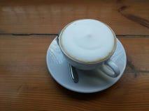 在木桌上的拿铁咖啡 库存图片