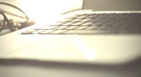 在木桌上的接近的膝上型计算机键盘在与太阳光的窗口附近在办公室工作场所在早晨 免版税图库摄影