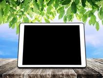 在木桌上的数字式片剂与绿色叶子和蓝天背景 图库摄影