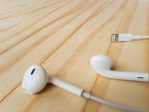 在木桌上的新的苹果计算机闪电EarPods 免版税库存图片