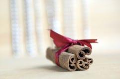 在木桌上的新鲜的未加工的肉桂条栓与红色弓,在背景的反射 库存图片