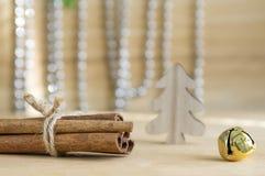 在木桌上的新鲜的未加工的肉桂条栓与红色弓,门铃,在背景的反射 免版税库存图片