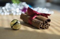 在木桌上的新鲜的未加工的肉桂条栓与红色弓,门铃,在背景的反射 库存图片