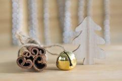 在木桌上的新鲜的未加工的肉桂条栓与红色弓,门铃,在背景的反射 免版税库存照片