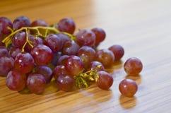 在木桌上的新鲜的红葡萄 图库摄影