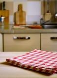 在木桌上的方格的桌布在厨房 库存照片