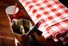 在木桌上的方格的餐巾与红色咖啡杯 免版税库存照片