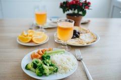 在木桌上的早餐 薄煎饼,桔子,新鲜的橙汁,黄瓜,蕃茄,米,硬花甘蓝,肉,花 图库摄影
