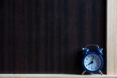 在木桌上的时钟在黑板附近 研究概念 库存照片