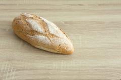在木桌上的有壳的大面包面包 库存照片