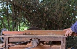 在木桌上的木匠工具与圆的锯木屑看见了 鲤鱼 库存照片