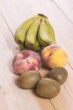 在木桌上的果子 香蕉、桃子和猕猴桃 免版税库存图片