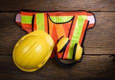 在木桌上的标准建筑安全设备 免版税库存照片