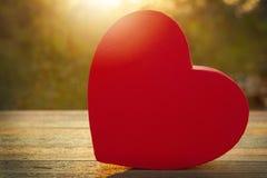 在木桌上的桃红色心脏礼物盒在日落 免版税库存照片