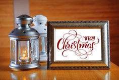 在木桌上的框架与文本圣诞快乐 书法字法 免版税库存图片