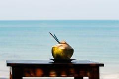 在木桌上的椰子震动与海在背景中 免版税库存照片
