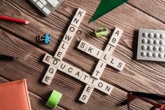 在木桌上的概念性主题词与做纵横填字谜的比赛的元素 免版税图库摄影