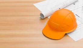 在木桌上的橙色或棕色安全帽与图纸 焊工和工作者的安全帽有高温应用的 免版税库存图片