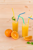 在木桌上的橙色新鲜的汁液 免版税库存图片