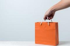 在木桌上的橙色购物袋 库存图片