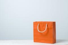 在木桌上的橙色购物袋 库存照片