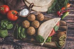 在木桌上的沙拉三明治、新鲜蔬菜、调味汁和皮塔饼面包 免版税库存照片