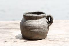 在木桌上的泥罐在自然光 免版税图库摄影