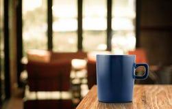 在木桌上的深蓝咖啡杯在迷离咖啡馆背景中 库存图片