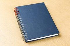 在木桌上的深蓝笔记本 库存图片