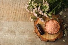 在木桌上的温泉构成 自然芳香油,在土气木背景的海盐 健康护肤 温泉概念 顶视图 免版税库存图片
