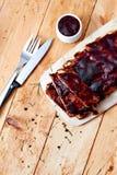 在木桌上的烤肉肋骨用调味汁 免版税库存图片