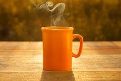 在木桌上的热的咖啡在日落 免版税库存照片