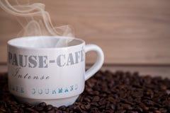 在木桌上的热的咖啡杯 图库摄影