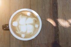 在木桌上的热的拿铁在早晨光 库存照片