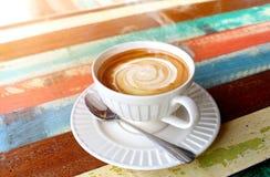 在木桌上的热的热奶咖啡咖啡 图库摄影