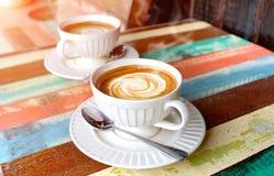 在木桌上的热的热奶咖啡咖啡 免版税图库摄影
