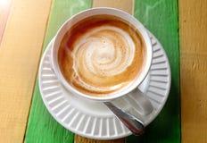 在木桌上的热的热奶咖啡咖啡 免版税库存照片