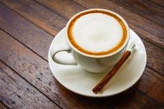 在木桌上的热的牛奶咖啡 免版税图库摄影
