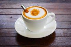 在木桌上的热的牛奶咖啡 库存图片