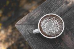 在木桌上的热的绿茶拿铁艺术 免版税库存图片