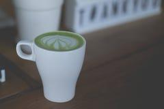 在木桌上的热的绿茶拿铁艺术 免版税图库摄影