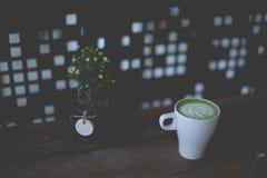 在木桌上的热的绿茶拿铁艺术 免版税库存照片
