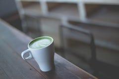 在木桌上的热的绿茶拿铁艺术 库存图片