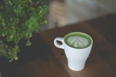 在木桌上的热的绿茶拿铁艺术 库存照片