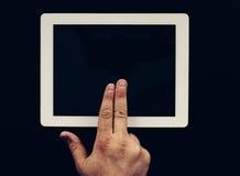 在木桌上的片剂与对此的手手指 免版税库存图片