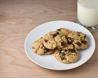 在木桌上的牛奶和巧克力片或者大块曲奇饼 库存照片