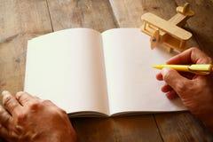 在木桌上的玩具飞机旁边张开空白的笔记本和人手 减速火箭的样式被过滤的图象 库存照片