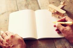 在木桌上的玩具飞机旁边张开空白的笔记本和妇女手 减速火箭的样式被过滤的图象 库存图片