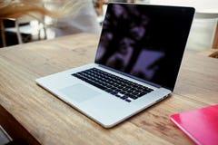 在木桌上的现代笔记本在露天大阳台咖啡店 免版税库存照片