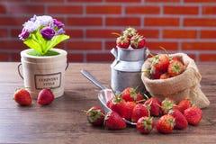 在木桌上的甜草莓与装饰和橙色砖墙 库存照片